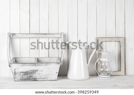 Rustic still life in white color: shabby wood box and photo frame, jug and lantern against white wood wall. - stock photo