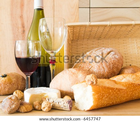 Rustic still life of breads, Camembert cheese, wine, and some figs against a wooden board, a wicker basket, and a sandstone wall.