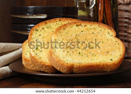 Rustic still life of freshly baked garlic bread seasoned with melted butter and herbs.  Olive oil and stoneware dishes in soft focus in background. - stock photo