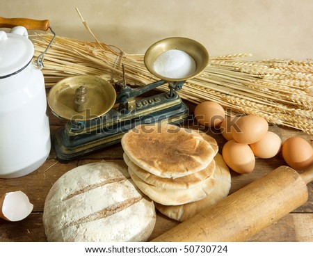 Rustic still life of vintage scales, bread, wheat, eggs and rolling pin - stock photo