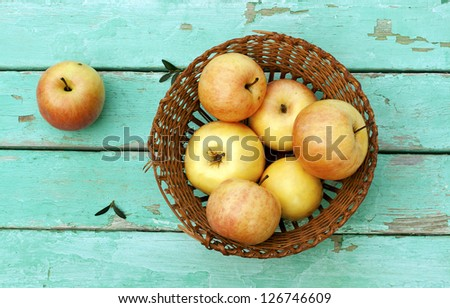 rustic still life with apples on basket on turquoise weathered wood - stock photo