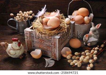 rustic still life with eggs in nest on vintage wooden box for easter  - stock photo
