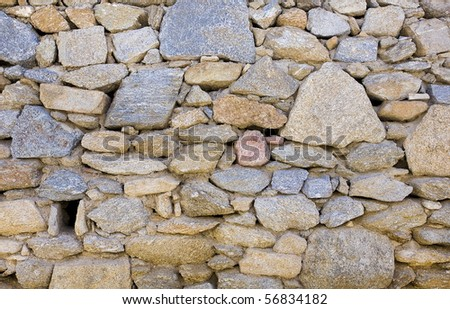 Rustic Stone Wall Of Raw Uncut Stones Background