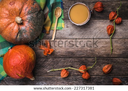 Rustic style pumpkins, soup and ground cherry branches on wood. Autumn Season food photo - stock photo