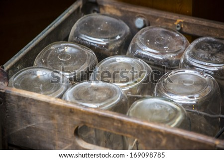 Rustic style wooden box with old fashion glass jars - stock photo