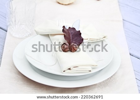 Rustic table decorated with leaves and acorns, ready for a Thanksgiving meal. - stock photo