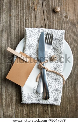 Rustic table setting on old wooden table with wooden decor - stock photo