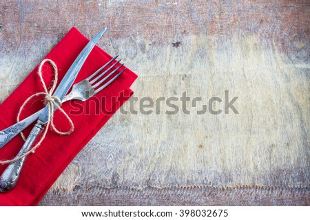 Rustic table setting with bright napkin and  silverware on old wooden table. View from above with copy space - stock photo