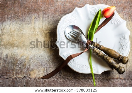 Rustic table setting with bright tulip flower, silverware and plate on old wooden table. View from above with copy space - stock photo