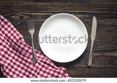 Rustic table setting with cutlery and red checkered napkin on dark wooden table. Space for text, top view.