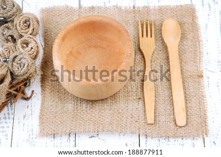 Rustic table setting with plate, fork and spoon, on wooden table - stock photo