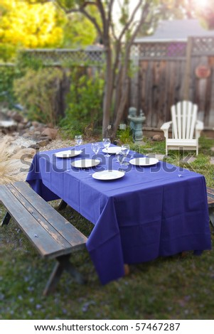Rustic table with purple cloth and dinner plates in a lush garden - stock photo