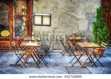 rustic tables and chairs by a trattoria in Florence, Italy - stock photo