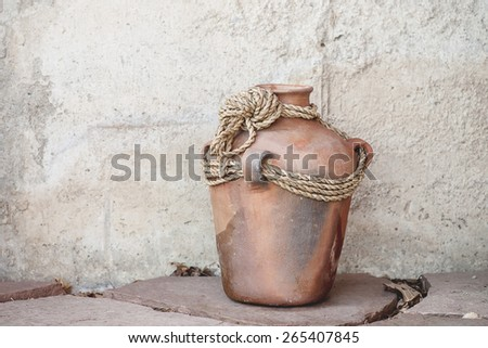 Rustic terracotta clay pot on slate and concrete background (Shallow DOF) - stock photo