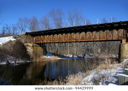 Rustic train bridge over river in winter time