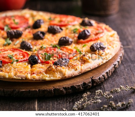 Rustic vegetarian pizza on wooden board - stock photo