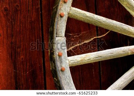 rustic wagon wheel hanging on a wall - stock photo