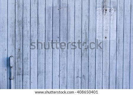 Rustic, weathered wooden-sided wall, painted light blue, with marks where signs have hung. Nicely textured and suitable as a background element.