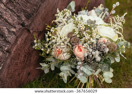 rustic wedding bouquet with roses and succulents on green grass and wooden texture