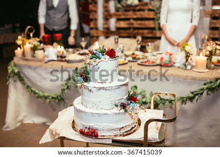 rustic wedding cake on wedding banquet with red rose and other flowers - stock photo