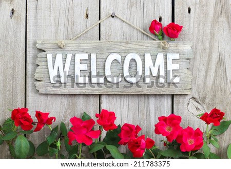 Rustic welcome sign hanging on wood fence with flower border of red roses - stock photo