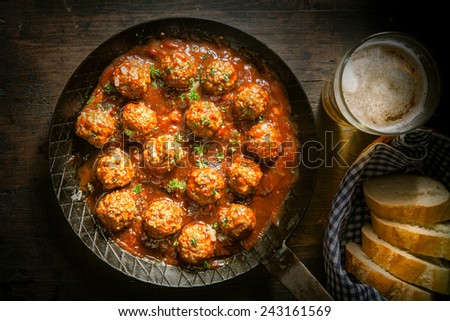 Rustic wholesome lunch of tasty savory meatballs in a spicy tomato and herb sauce served with a glass of beer and sliced baguette, close up overhead view - stock photo