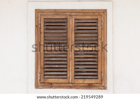 rustic window closed with wooden exterior shutters - stock photo