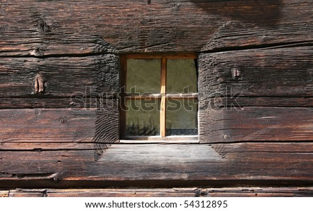 Rustic window on an old wooden house - stock photo
