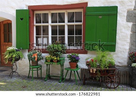 rustic window with green shutters and flower pots in white rural house, Switzerland. - stock photo