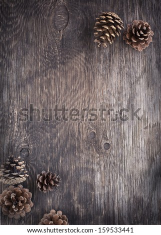 Rustic wood background with pine cones - stock photo
