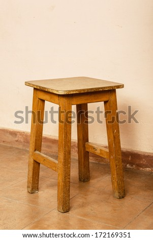 Rustic wood stool, pink wall background - stock photo
