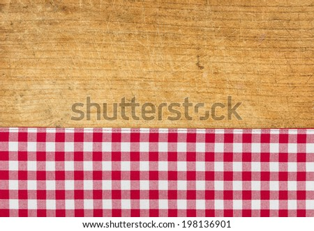 Rustic wooden background with a red checkered tablecloth - stock photo