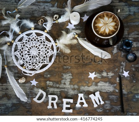 Rustic wooden background with boho chic style decorations: dreamctcher, cup of cappuccino, pens and paper stars. Copy space for text. Natural, rustic, ethnic or hipster vintage mock up. Top view.  - stock photo