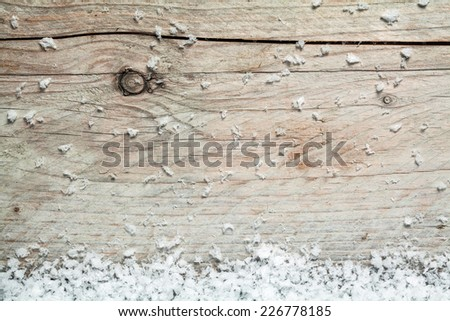 Rustic wooden background with winter snow on the bottom border and plenty of copyspace for your seasonal or Christmas greeting or invitation - stock photo