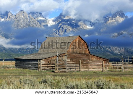Rustic wooden barn with the Teton mountains, Wyoming, USA. - stock photo