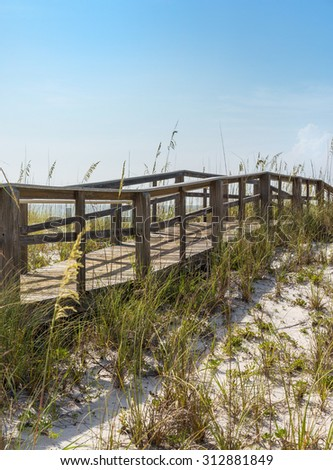 Rustic wooden boardwalk in hilly dunes at beach in Florida - stock photo