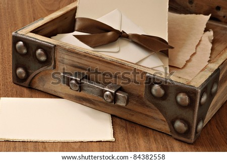 Rustic wooden desk drawer with parchment stationery and envelopes tied with satin ribbon. Blank note card included in composition for copy space.  Macro with shallow dof. - stock photo