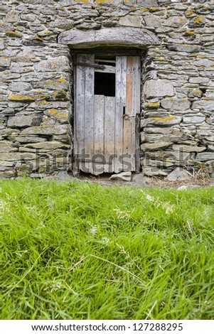 Rustic wooden door on stone barn in Cumbria, England, UK
