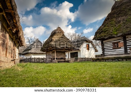 Rustic wooden houses with thatched roofs in a village of rural eastern europe against the blue sky and some clouds in Bucharest, Romania - stock photo