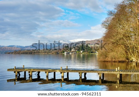 Rustic wooden jetty extending out over peaceful waters in Windermere, English Lake Disrtict.