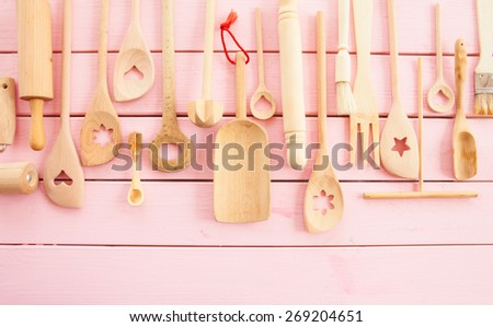 Rustic wooden kitchen utensils  on pink wooden boards - stock photo