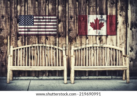Rustic wooden log benches side by side against a wall of wooden siding with United States of America and Canada flags imprinted above the benches.  Filtered for a retro, vintage look.  - stock photo