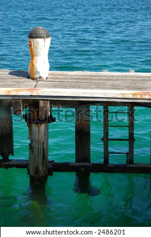 Rustic wooden pier with turquoise water - stock photo