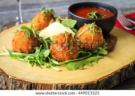 Rustic wooden plate with fried risotto balls sitting on bed of micro green with parmesan cheese garnish and marinara sauce for dipping