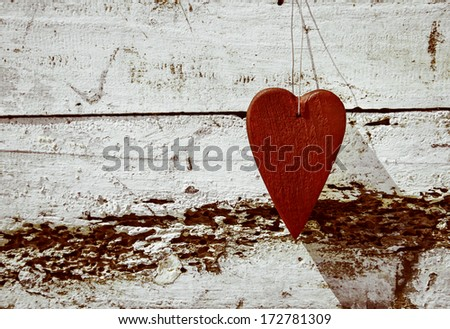 Rustic wooden red heart hanging on the weathered old white wood - stock photo