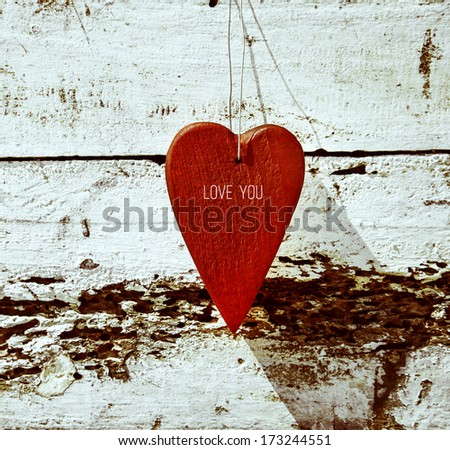 "Rustic wooden red heart hanging on the weathered old white wood with text ""Love you"" - stock photo"