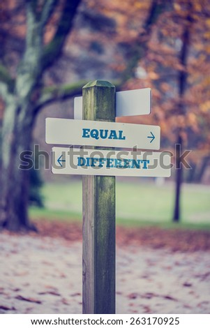 Rustic wooden sign in an autumn park with the words Equal - Different offering a choice of attitude with arrows pointing in opposite directions in a conceptual image with a vintage style filter effect - stock photo