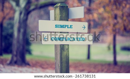 Rustic wooden sign in an autumn park with the words Simple - Complicated offering a choice of action and attitude with arrows pointing in opposite directions in a conceptual image. - stock photo