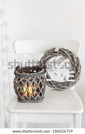 Rustic wreath and lantern on a white shabby chic chair near the wall - stock photo