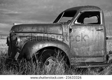 Rusting farm truck in the grass field - stock photo